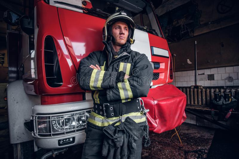 Young fireman wearing protective uniform standing next to a fire engine in a garage of a fire department. Portrait of a brave young fireman wearing protective royalty free stock photography