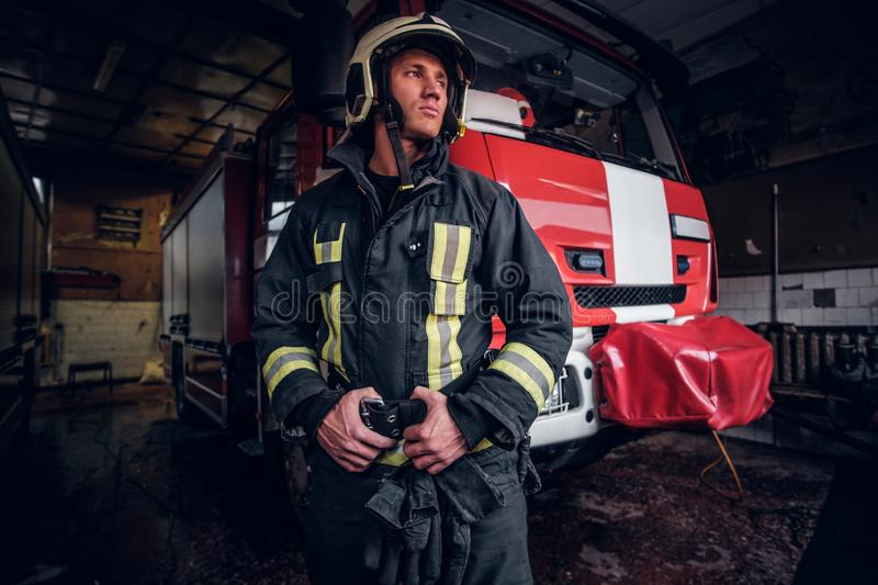 Young fireman wearing protective uniform standing next to a fire engine in a garage of a fire department. Portrait of a brave young fireman wearing protective stock image