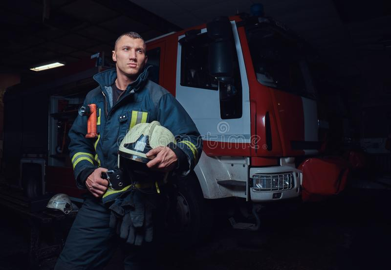 Young fireman wearing protective uniform standing next to a fire engine in a garage of a fire department. Portrait of a brave young fireman wearing protective stock photography