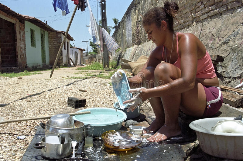 Portrait of Brazilian women when washing the dishes. Brazil, state Pernambuco, Recife city: street from one of the most criminal slums of the city barrio of stock photography
