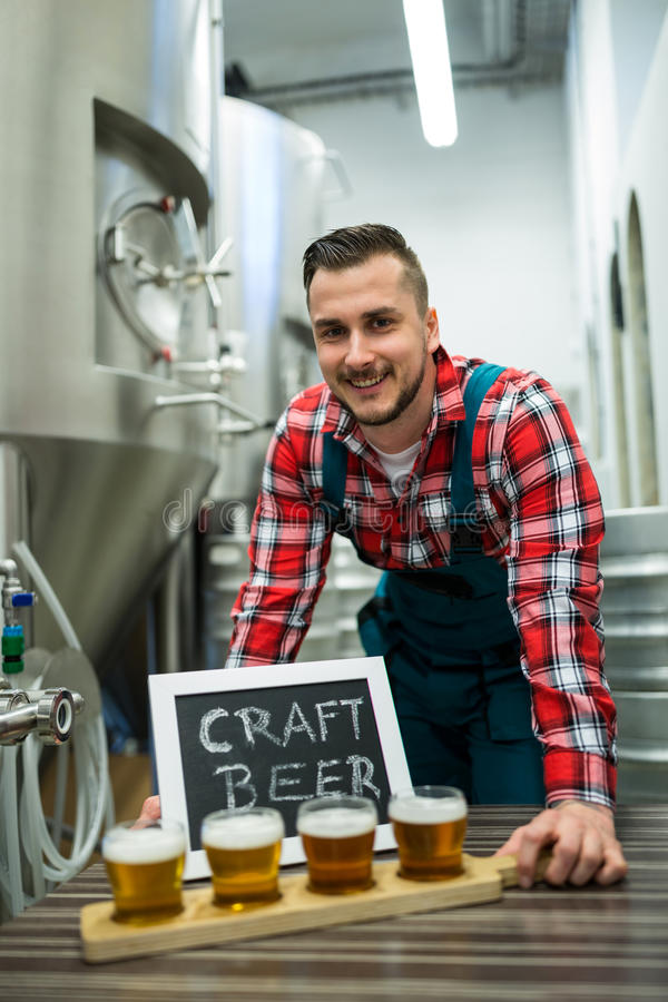 Portrait of brewer with four glasses of craft beer on table. Portrait of happy brewer with four glasses of craft beer on table at brewery royalty free stock photo