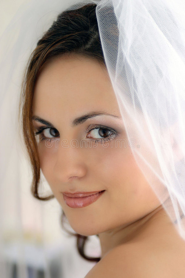 Portrait of a Bride. A portrait of a Bride pictured on her wedding day. She is wearing a traditional white wedding dress with a veil, and is seen here smiling at royalty free stock images