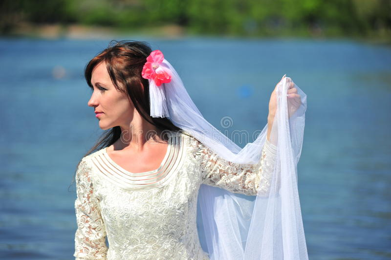 Portrait of the bride against lake. Portrait of the bride with a veil against lake royalty free stock photo