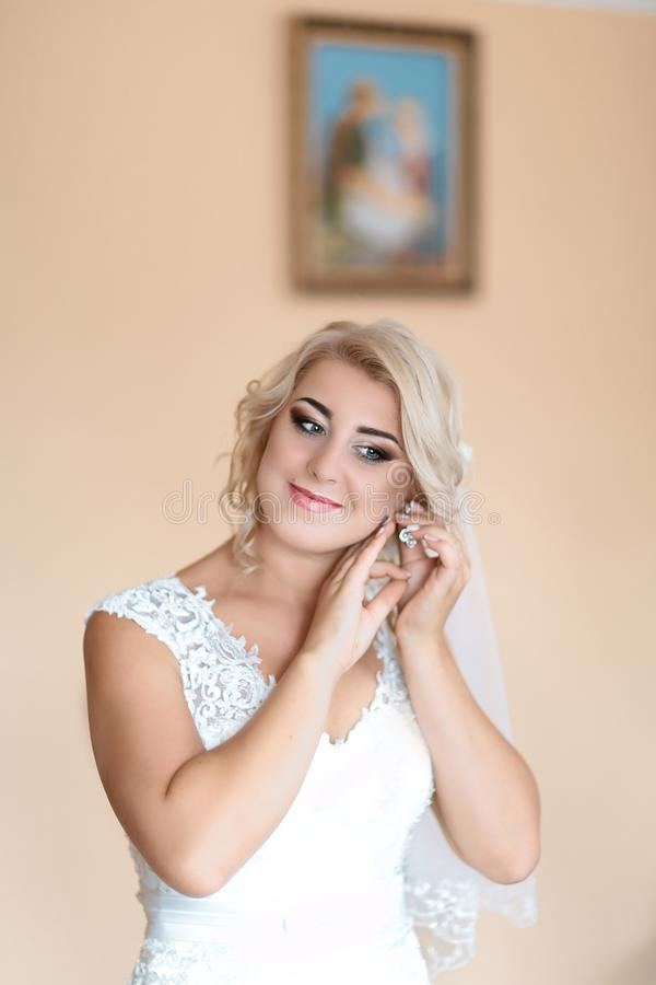 Portrait of the bride as wearing earrings in a white wedding dress. beauty and jewelery concept stock photo