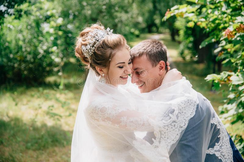 Portrait of the bride and groom hugging and laughing in the park. A girl in a white lace veil embraces her man and royalty free stock photos