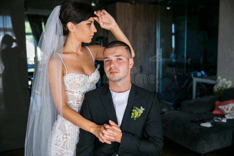 Portrait of the bride and groom in the interior. The groom sits and looks into the camera, holding the bride by the hand. The bride straightens her hair and stock photos