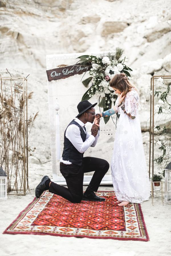 Portrait of bride and groom looking to each other near the wedding arch in boho rustic style. African young man is royalty free stock photography
