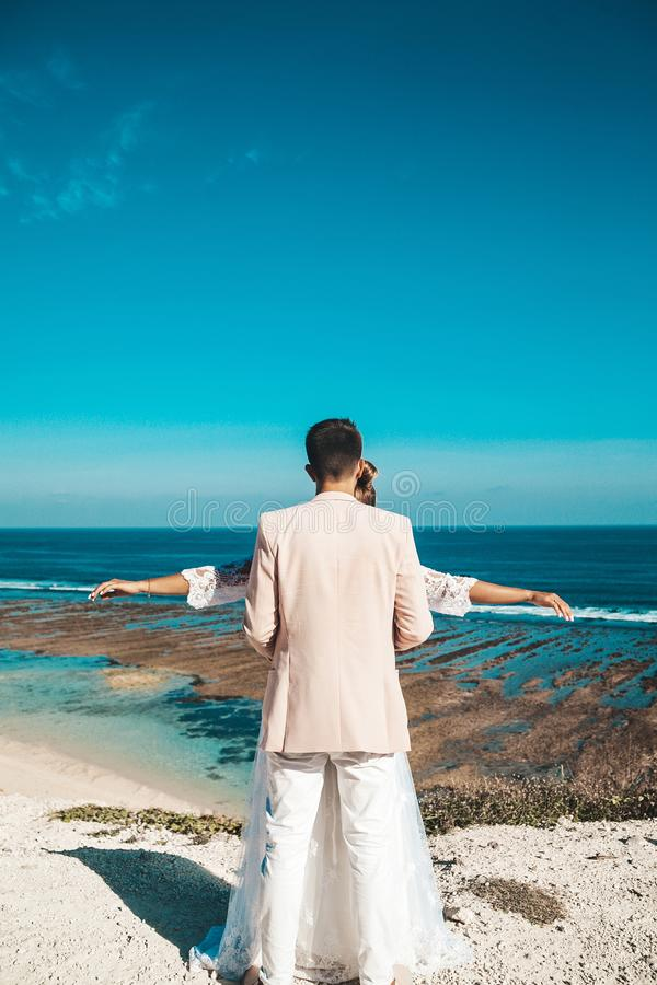 Bride and groom posing on the cliff behind blue sky and sea. Wedding Couple royalty free stock photo