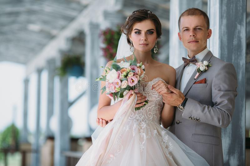 Portrait of the bride and groom on wedding day. The groom in a gray business suit holds the bride in a white luxury stock images