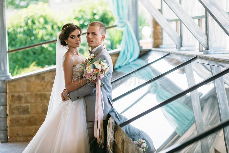 Portrait of the bride and groom on wedding day. The groom in a gray business suit holds the bride in a white luxury. Dress with a veil for the hand. Woman with stock images