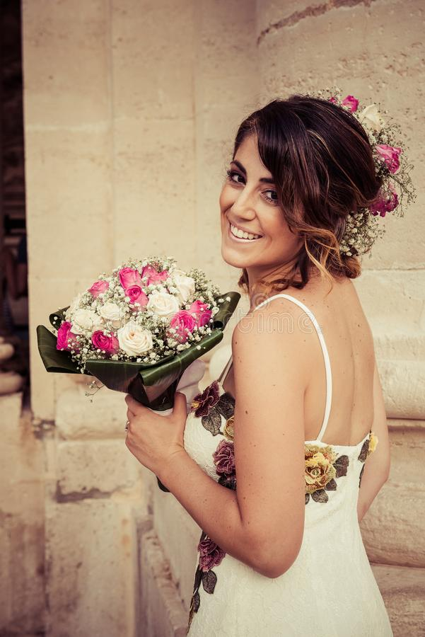 Portrait of a Bride Iin Front of Siracusa`s Cathedral. A girl, on the day of her wedding, white dressed, is posing . On the background, the doric column of royalty free stock photo