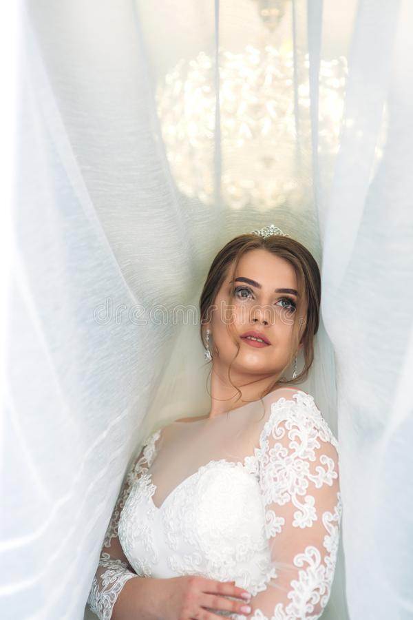 Portrait of a bride in a wedding dress under the white curtain royalty free stock photography
