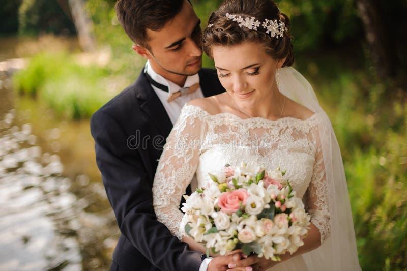Portrait of a bridegroom embracing a bride stock photo