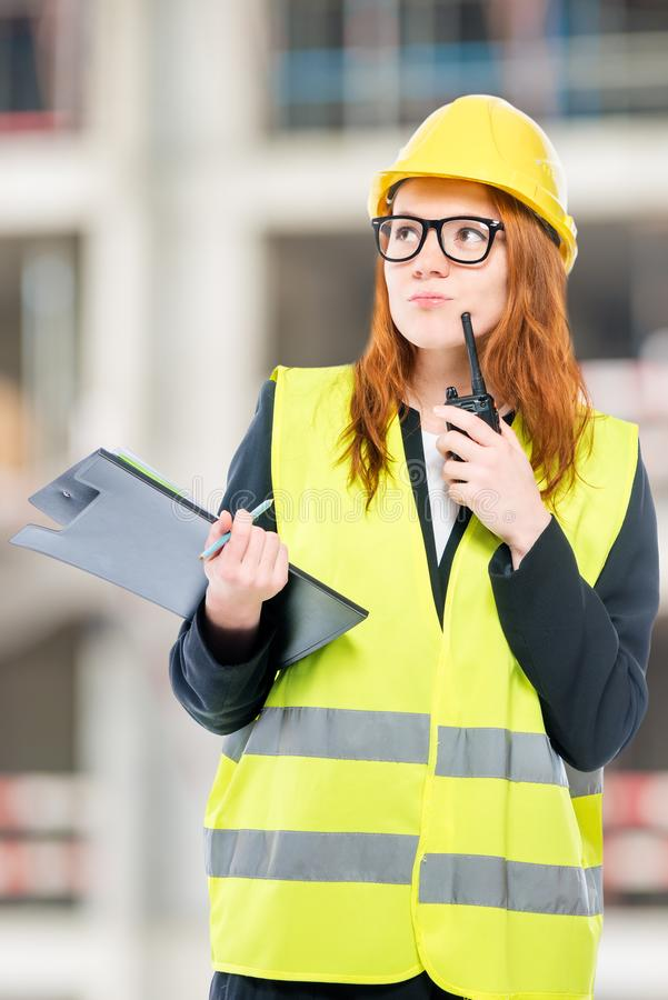 Portrait of a brigadier woman with a walkie-talkie. On a construction site royalty free stock photo