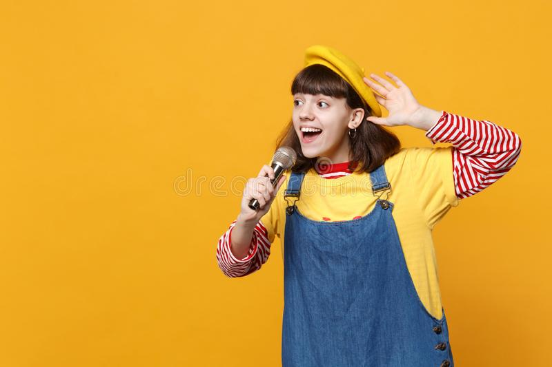 Portrait of bright girl teenager in french beret, denim sundress sing song in microphone isolated on yellow wall royalty free stock photography