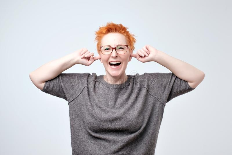 Portrait of bright mature caucasain woman with red hair covering ears with hands stock images