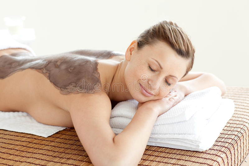 Portrait of a bright woman enjoying a mud skin tre. Atment in a Spa center stock image