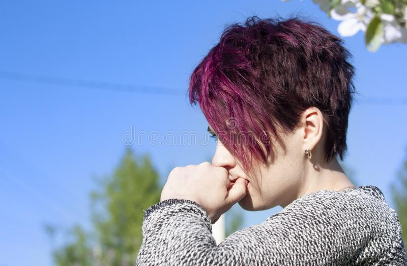 Portrait of a brooding girl with short-cropped pink hair stock images