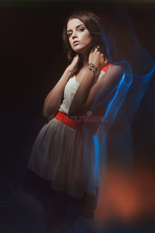 Portrait brouillé d'art de couleur d'une fille sur un fond foncé Façonnez la femme avec le beau maquillage et une robe légère d'é images libres de droits