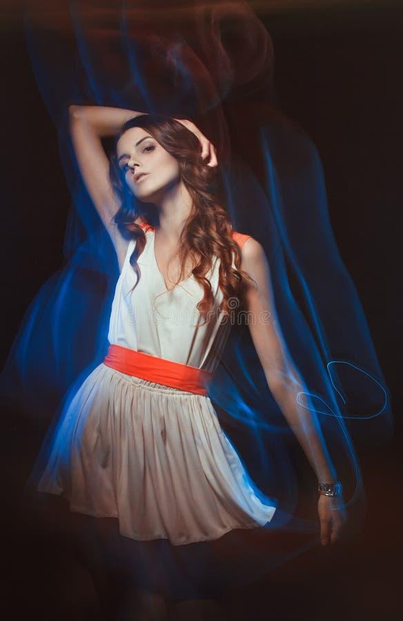 Portrait brouillé d'art de couleur d'une fille sur un fond foncé Façonnez la femme avec le beau maquillage et une robe légère d'é photo stock