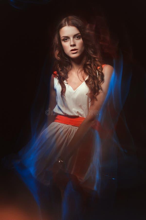Portrait brouillé d'art de couleur d'une fille sur un fond foncé Façonnez la femme avec le beau maquillage et une robe légère d'é image stock