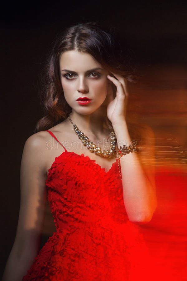 Portrait brouillé d'art de couleur d'une fille sur un fond foncé Façonnez la femme avec le beau maquillage et une robe légère d'é photographie stock