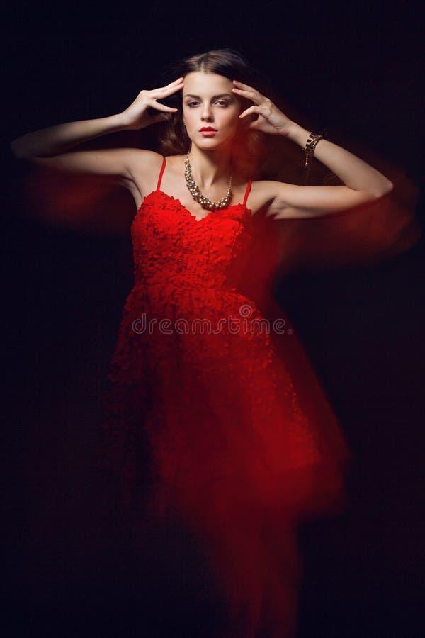 Portrait brouillé d'art de couleur d'une fille sur un fond foncé Façonnez la femme avec le beau maquillage et une robe légère d'é photos stock