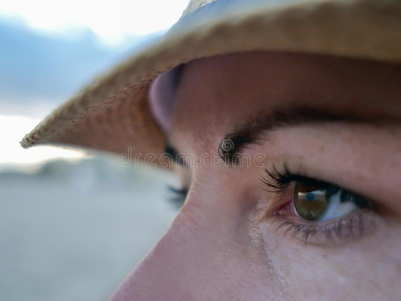 Portrait of a brown-eyed brunette in a hat looks to the side, close-up stock photography