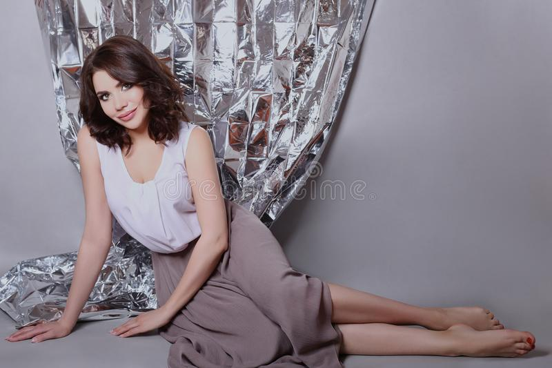 Portrait of a brown haired woman with a beautiful professional m. Akeup on a shiny background. girl with nice clean skin and bright lipstick on her lips stock image
