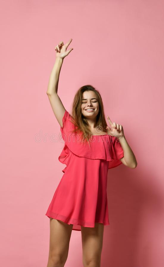 Portrait of brunette Caucasian girl dancing against pink wall with smile, rejoicing good mood. royalty free stock photos
