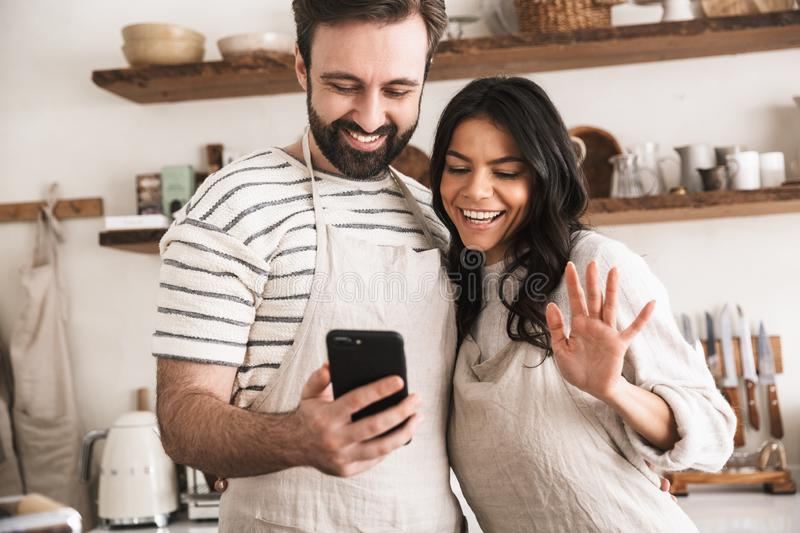 Portrait of brunette couple hugging together and holding smartphone while cooking in kitchen at home stock photography