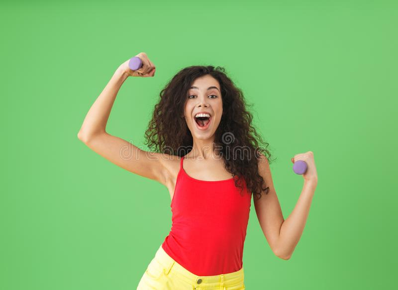 Portrait of brunette girl doing sports and lifting weights against green wall royalty free stock photography