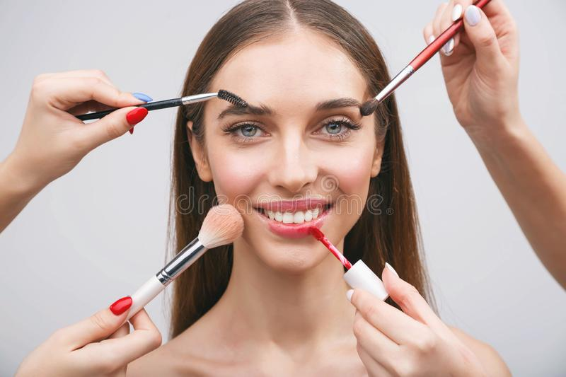 Hands Applying Makeup. Portrait of a brunette girl getting make-up applied by a makeup with many hands stock photos