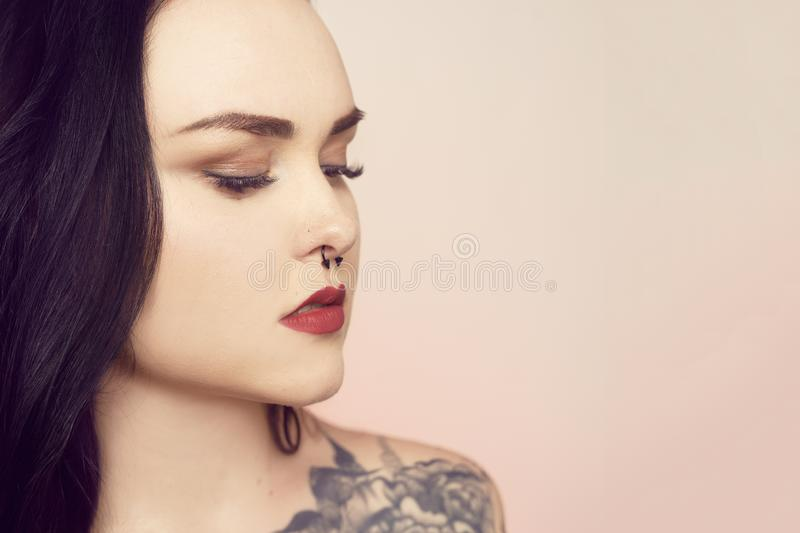 Portrait of a brunette with a pierced nose. Beautiful duvushka with a professional make-up. Woman with piercing in the nose at the bottom, an informal girl stock images