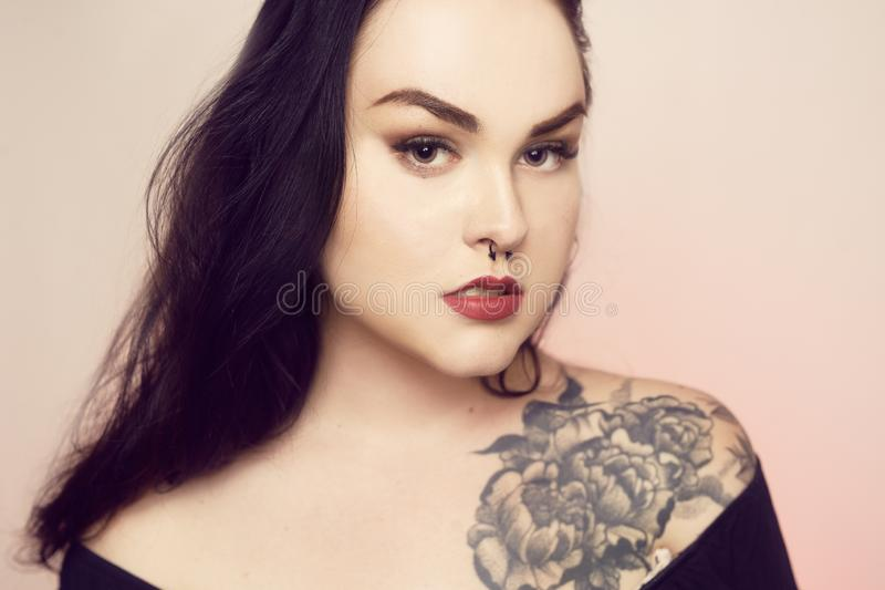 Portrait of a brunette with a pierced nose. Beautiful duvushka with a professional make-up. Woman with piercing in the nose at the bottom, an informal girl royalty free stock photography