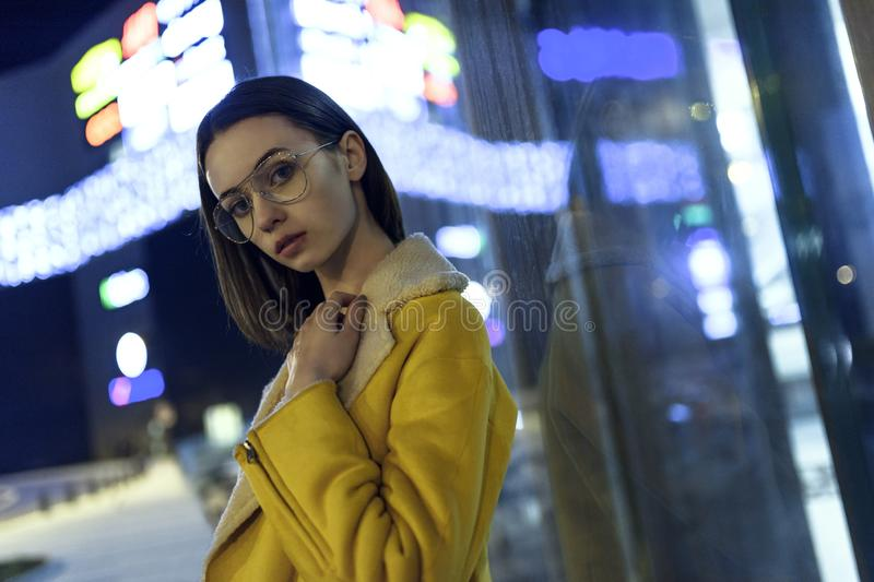 Portrait of brunette posing in stylish jacket and glasses, lit by city center lights by night. Womenswear fashion. Blurred royalty free stock photos