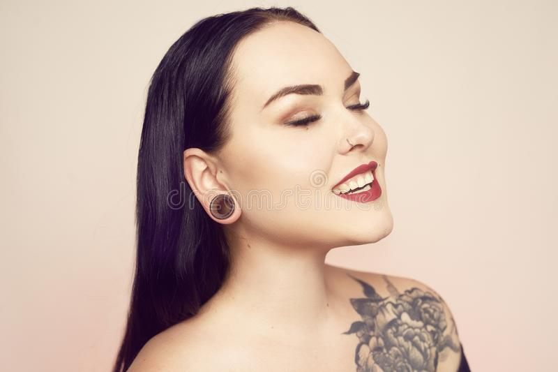 Portrait of a brunette with a tunnel in her ears, and a pierced nose. Beautiful duvushka with a professional make-up. Woman with. Piercing in the nose, informal stock images