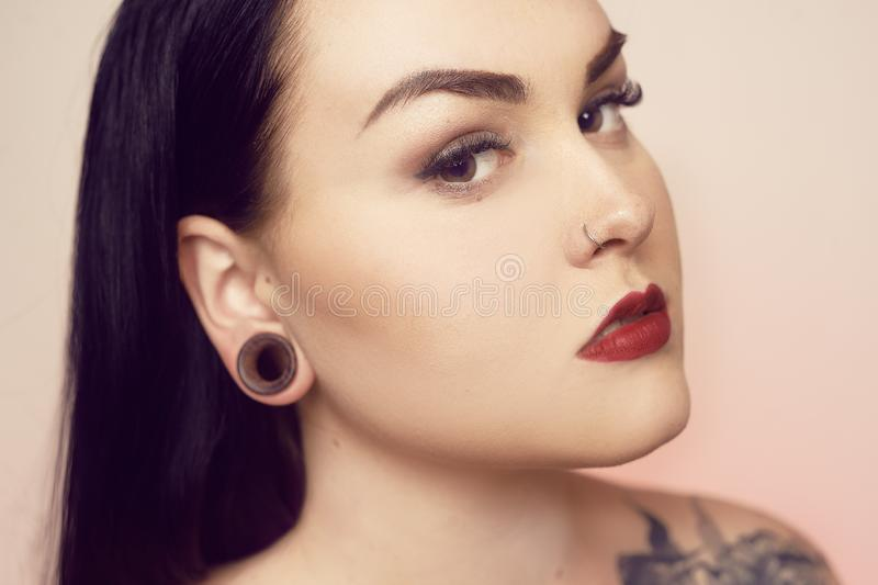 Portrait of a brunette with a tunnel in her ears, and a pierced nose. Beautiful duvushka with a professional make-up. Woman with. Piercing in the nose, informal royalty free stock photography