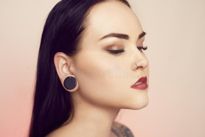 Portrait of a brunette with a tunnel in her ears, and a pierced nose. Beautiful duvushka with a professional make-up. Woman with. Piercing in the nose, informal royalty free stock photo