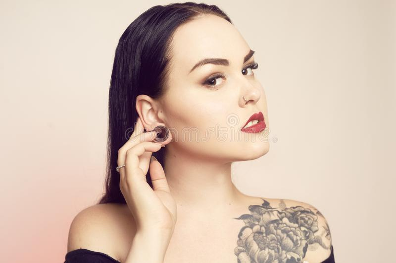 Portrait of a brunette with a tunnel in her ears, and a pierced nose. Beautiful duvushka with a professional make-up. Woman with. Piercing in the nose, informal stock photo