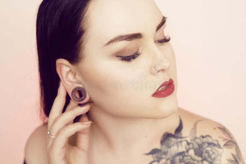 Portrait of a brunette with a tunnel in her ears, and a pierced nose. Beautiful duvushka with a professional make-up. Woman with. Piercing in the nose, informal stock photography