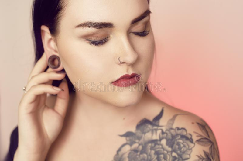 Portrait of a brunette with a tunnel in her ears, and a pierced nose. Beautiful duvushka with a professional make-up. Woman with. Piercing in the nose, informal stock photos