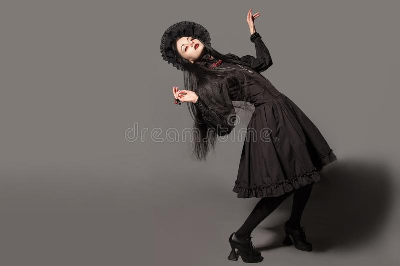 Portrait of brunette woman in black dress and classic gothic sty. Le with red eyes on gray background. halloween concept stock images