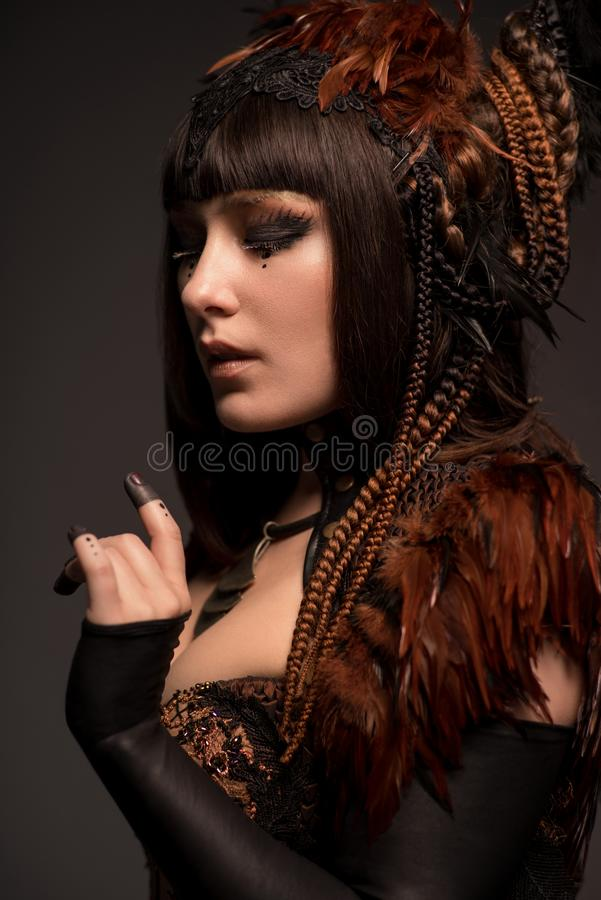 Portrait of brunette woman with dark gothic makeup and creative hairstyle. In studio stock images
