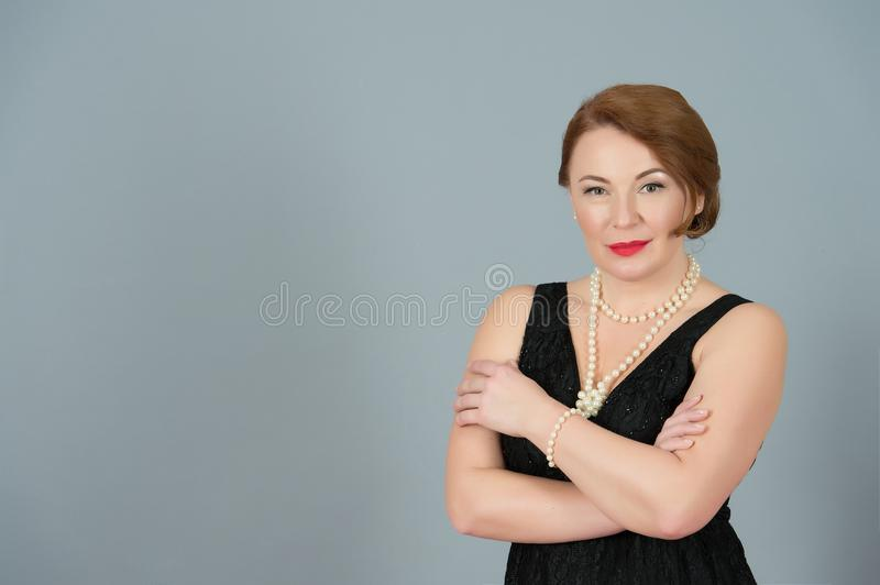 Portrait of American Brunette woman on grey background. Lady in black dress with perls and crossed hand on chest. stock photos