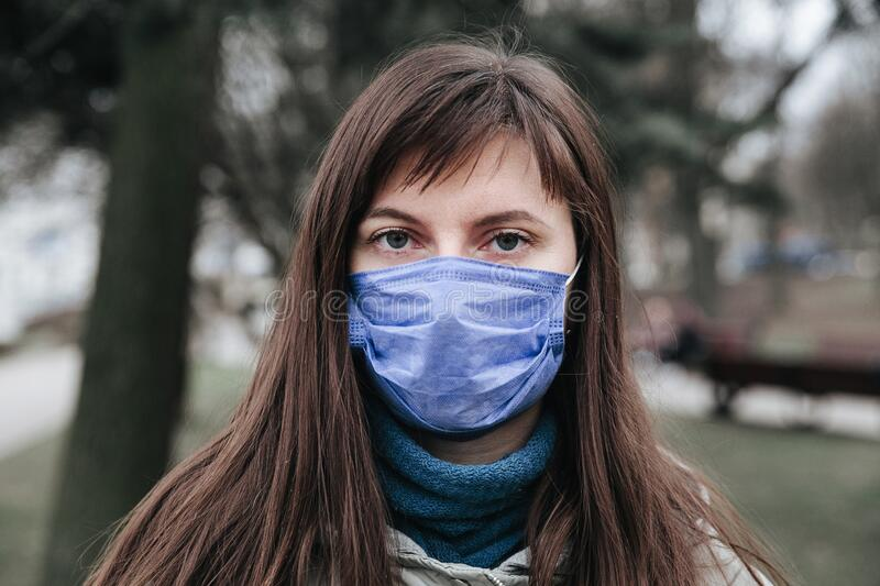 Portrait of brunette woman in a surgical bandage .Coronavirus epidemic, illness, infection, quarantine, medical mask. Portrait of brunette woman in protective stock photography