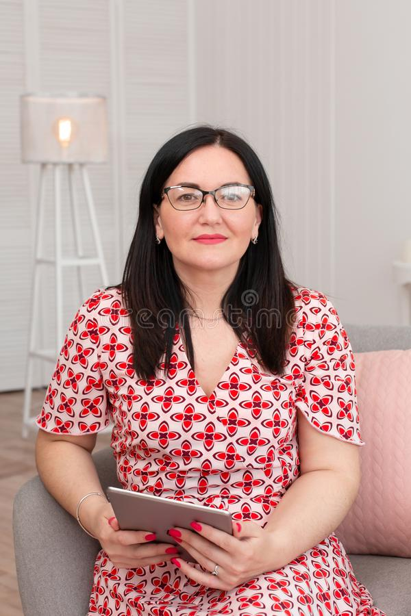 Portrait of a brunette woman in a red and white checkered dress, and glasses sits in a comfortable chair with an electronic tablet.  royalty free stock photos