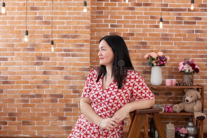 Portrait of a brunette woman in a red and white checkered dress posing against a brick wall.  royalty free stock photos