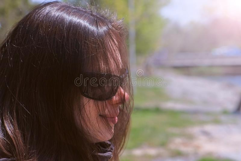 Portrait brunette woman in sunglasses looking at river in city park, side view. Portrait of brunette woman in sunglasses is looking at river in city park. She stock photos