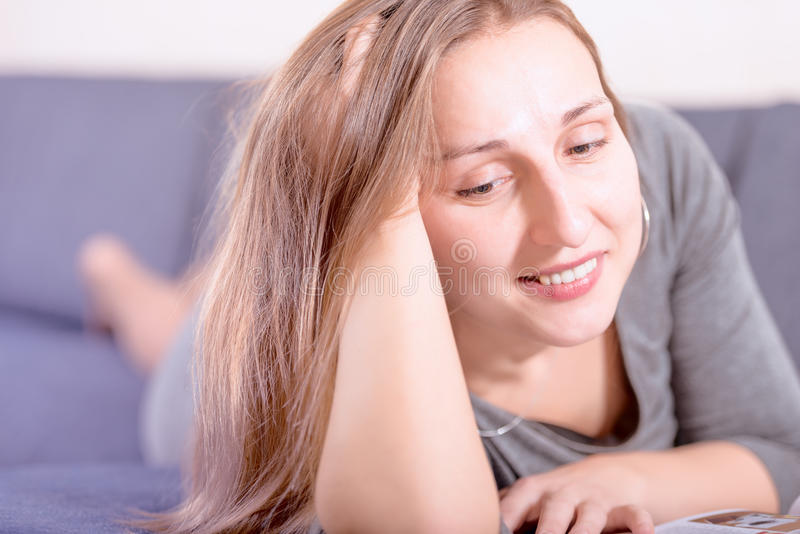 Portrait of brunette young woman reading on sofa royalty free stock images